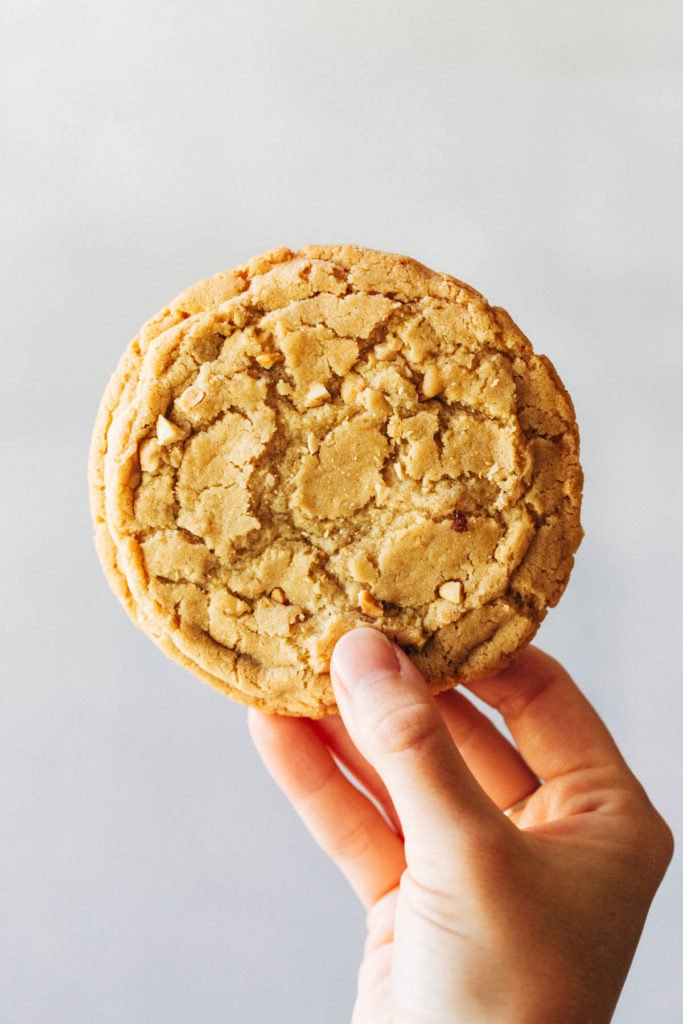 holding up a large peanut butter cookie