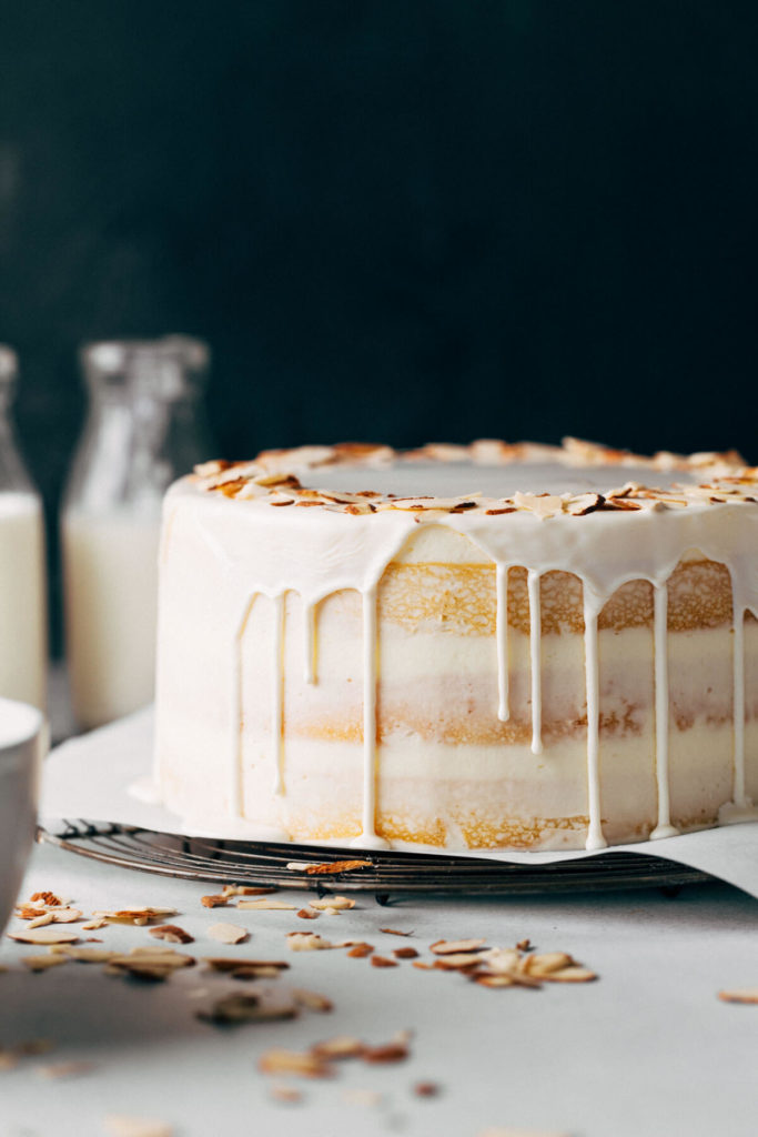 the side view of a layer cake with white chocolate dripping down the sides