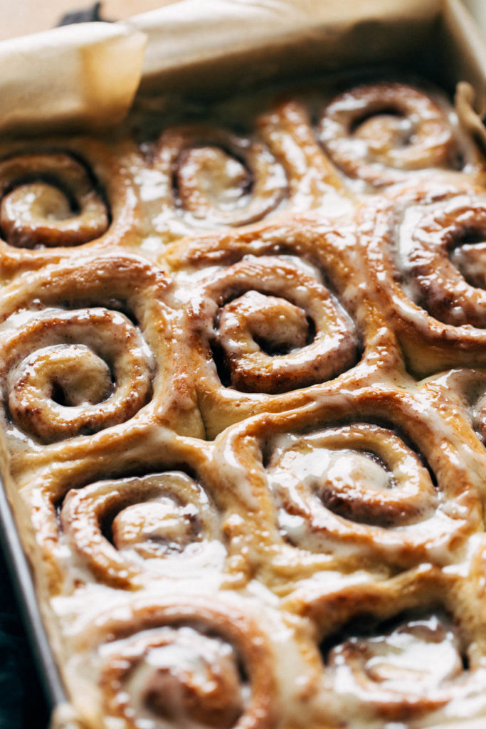 cinnamon rolls in a baking pan with glossy icing on top