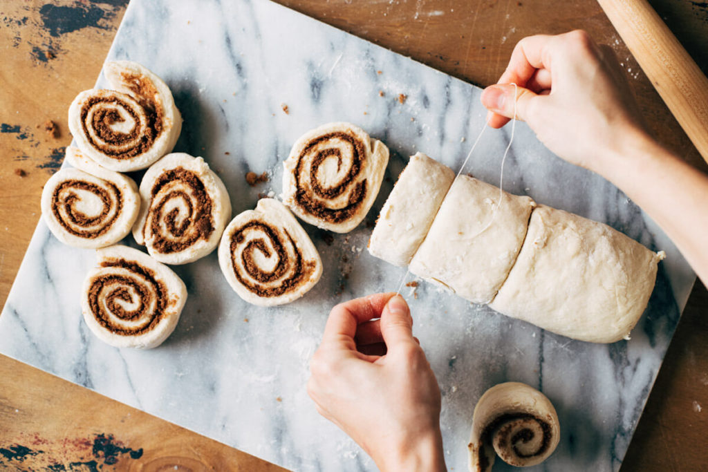 cutting cinnamon rolls with a piece of floss