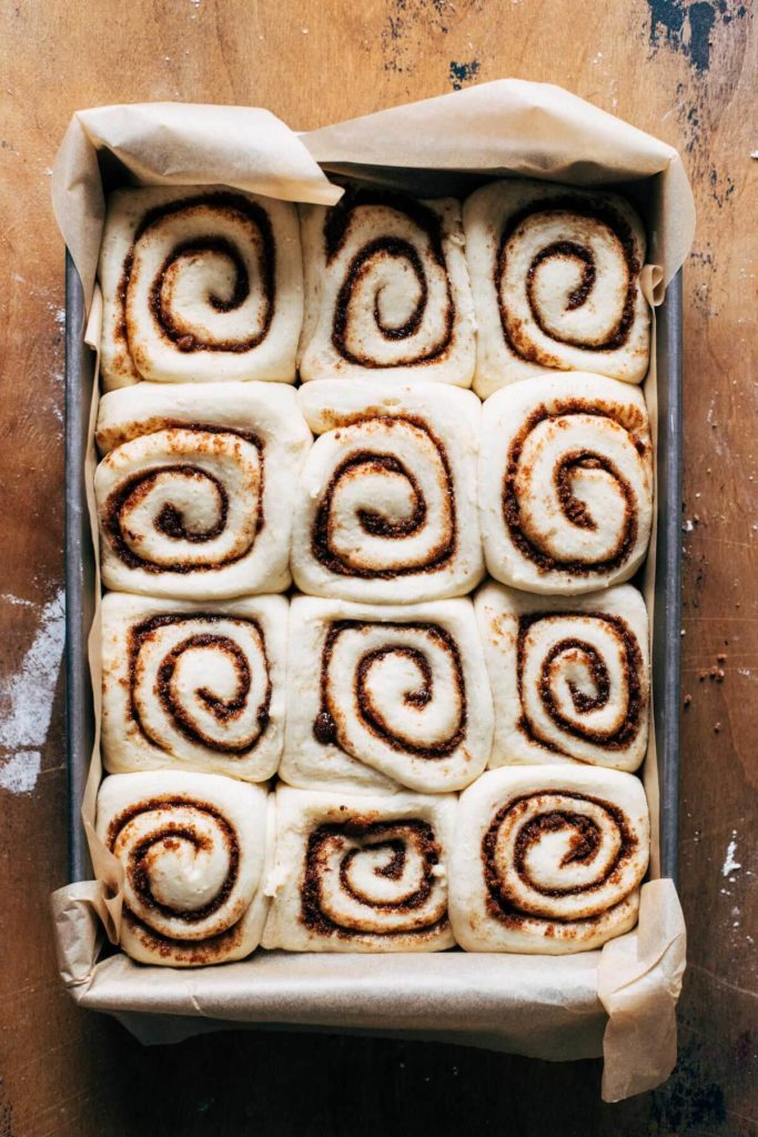 cinnamon rolls in a baking pan after proof
