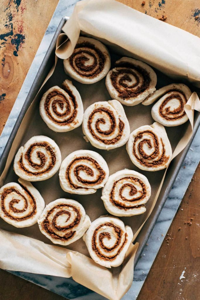 cinnamon rolls in a baking pan before proof