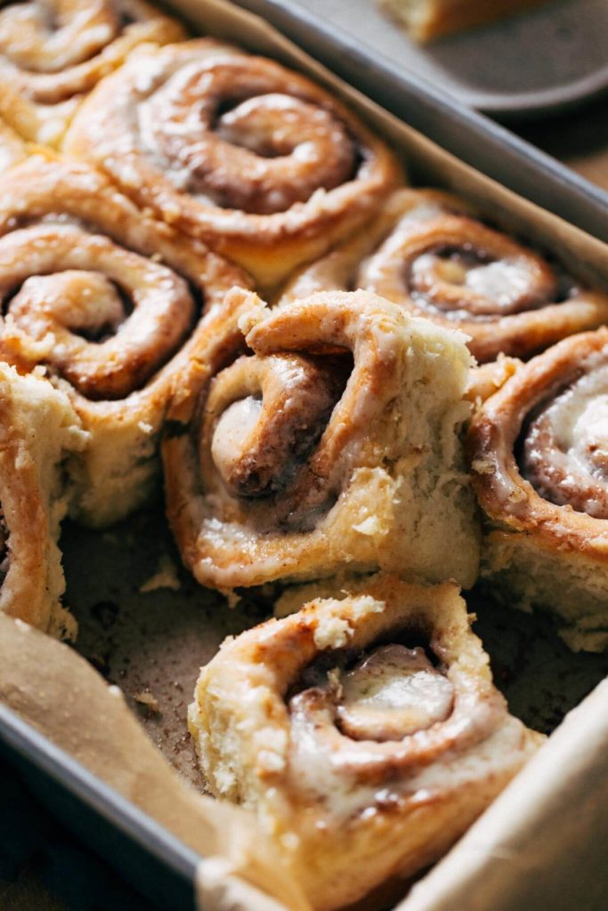 a cinnamon roll lifted out of a baking pan