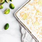 Coconut and lime sheet cake next to squeezed limes