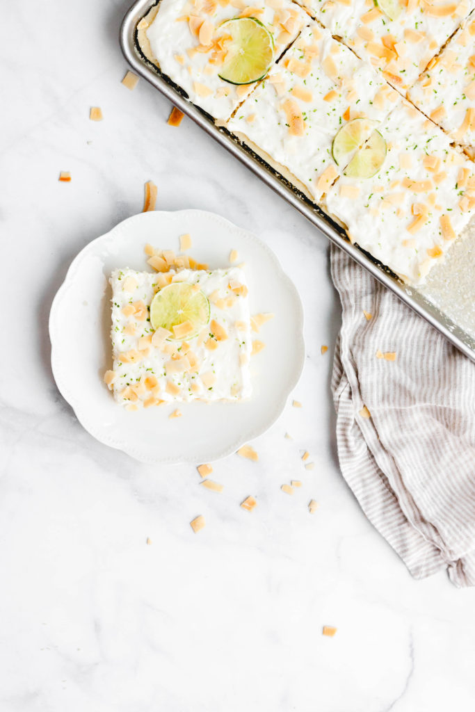 A piece of lime and coconut sheet cake on a plate.