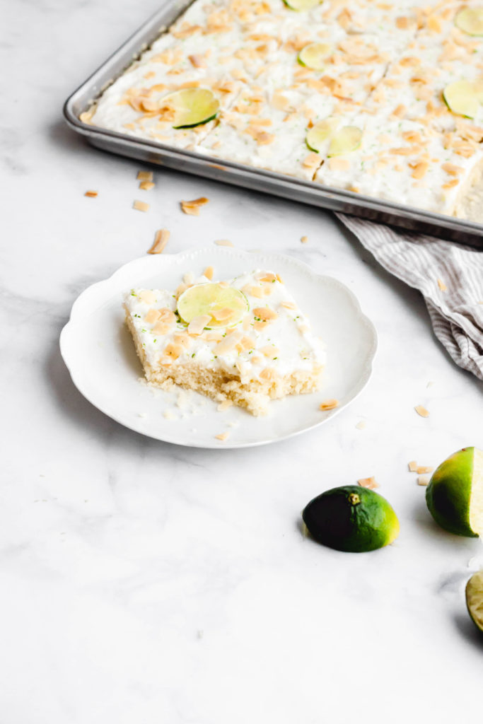 A piece of lime and coconut sheet cake on a plate with a bit taken out of it.