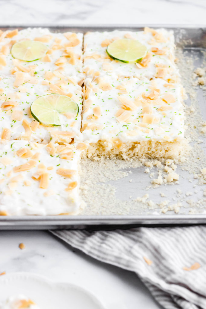 Coconut and lime sheet cake in a pan with some slices taken out.