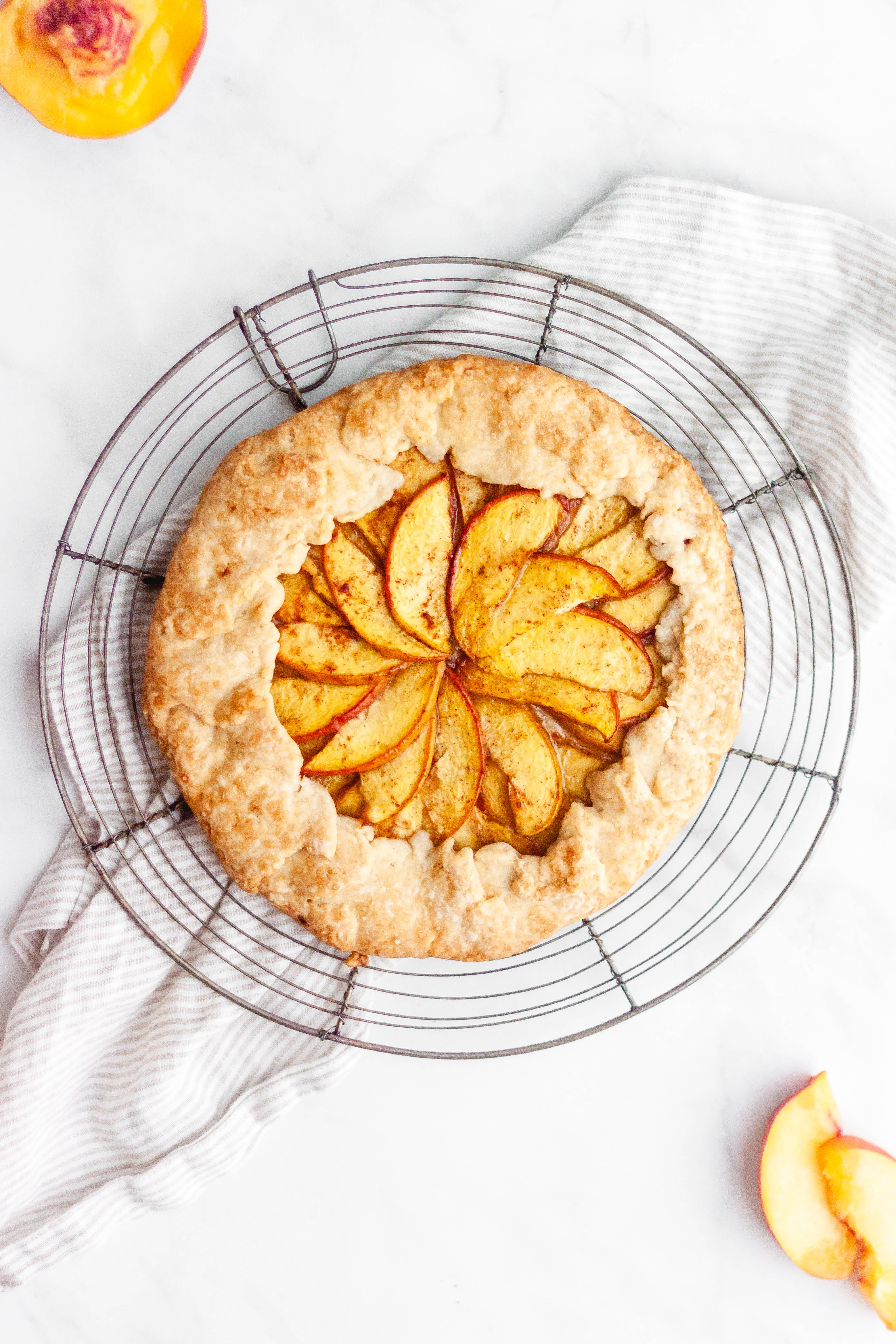 Summer peach galette on a round wire cooling rack