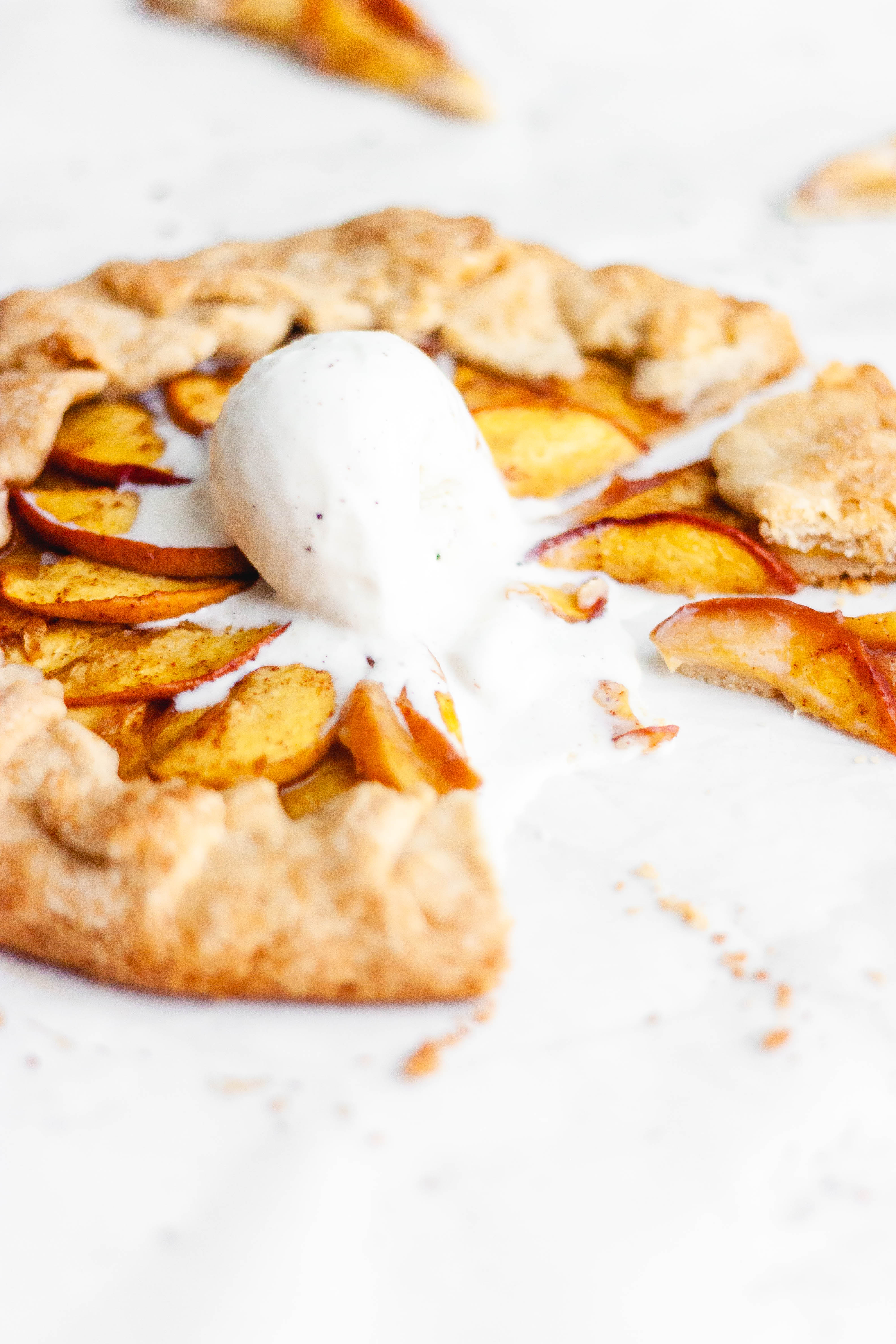 Sliced peach galette with a scoop of ice cream in the middle