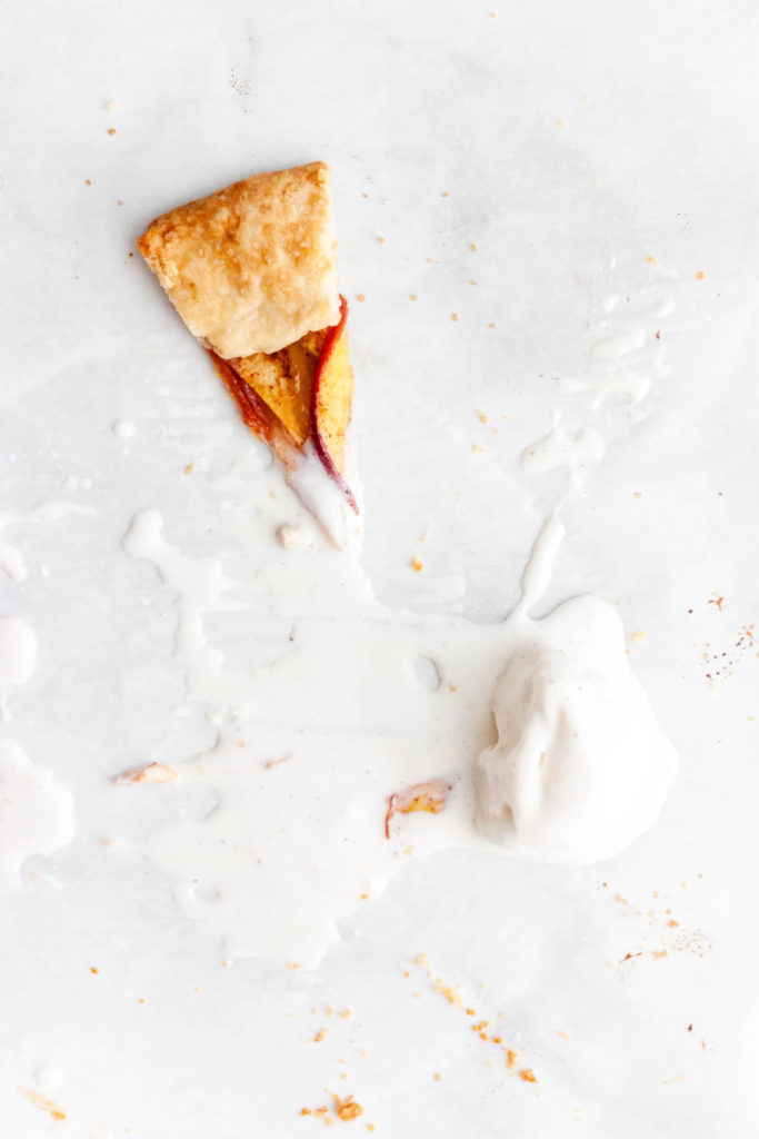 One slice of summer peach galette with a melted scoop of ice cream