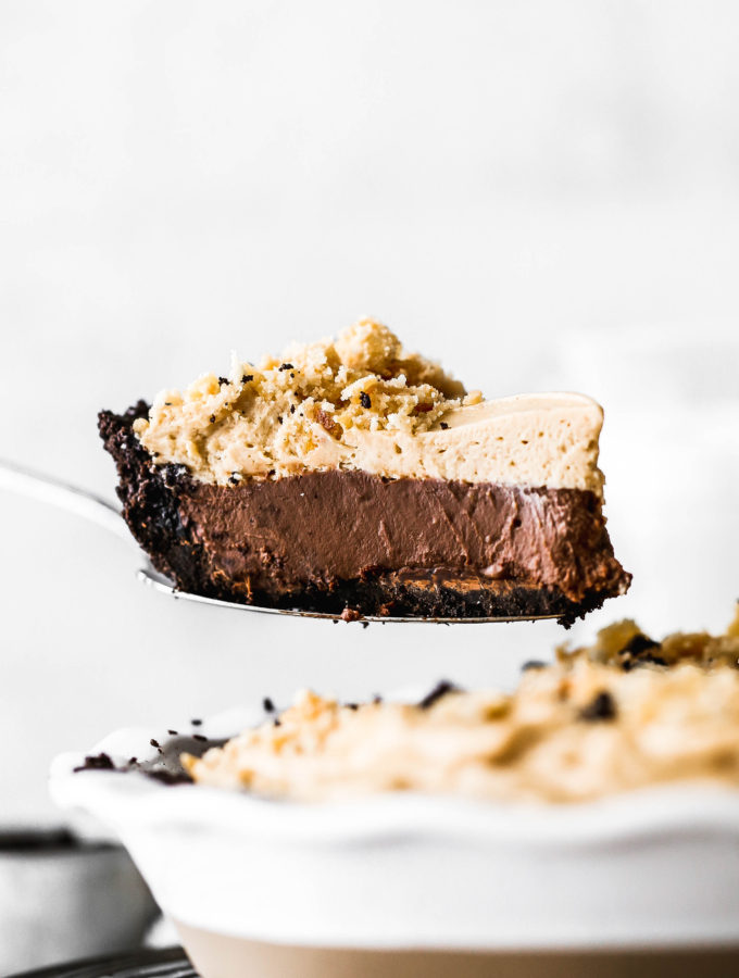 a slice of chocolate peanut butter pie being lifted out of the pie dish
