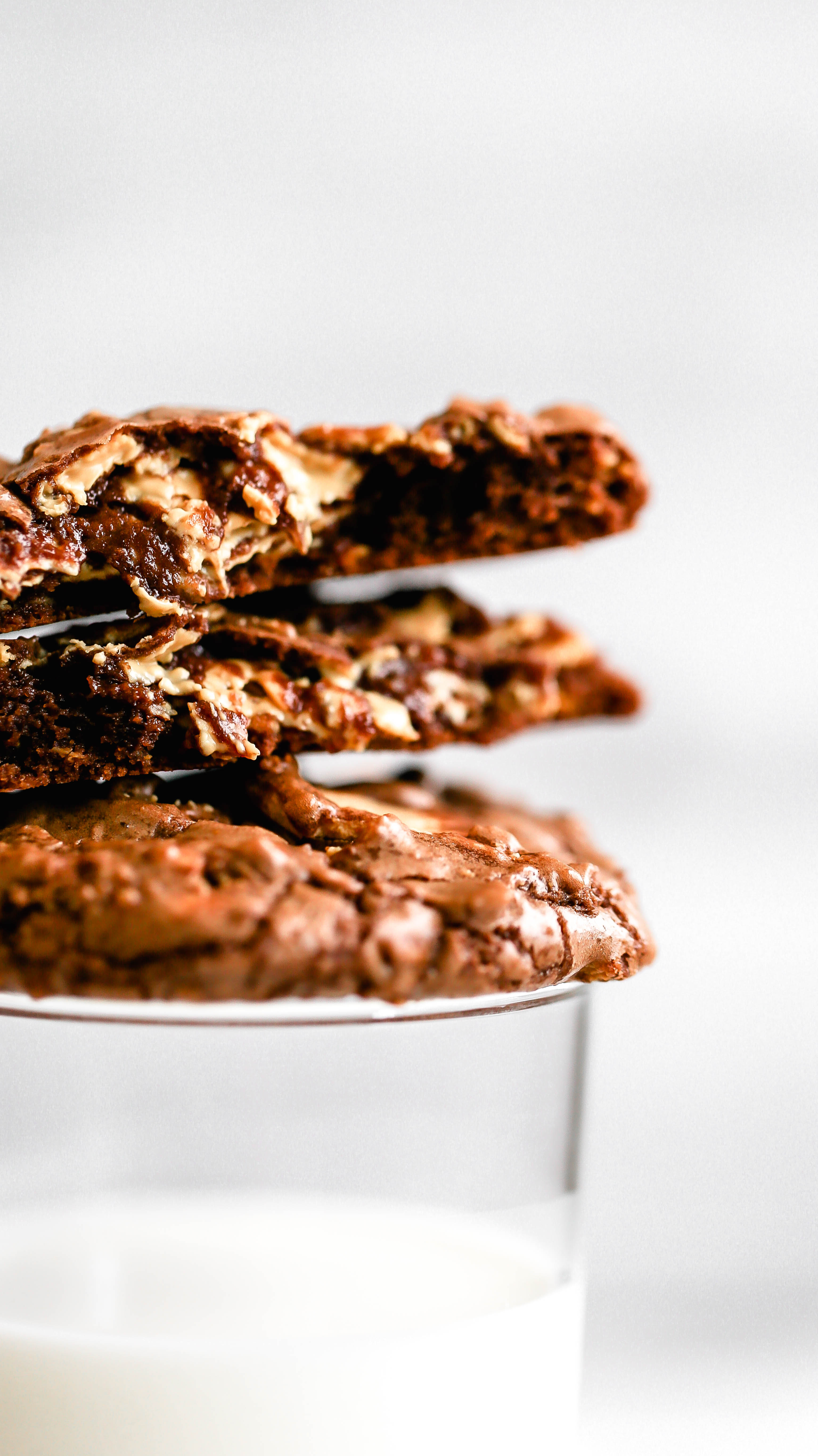 brownie cookies with caramelized white chocolate stacked on top of a glass of milk