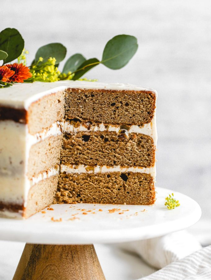 the inside of a spice cake with candied nuts and brown butter cream cheese frosting