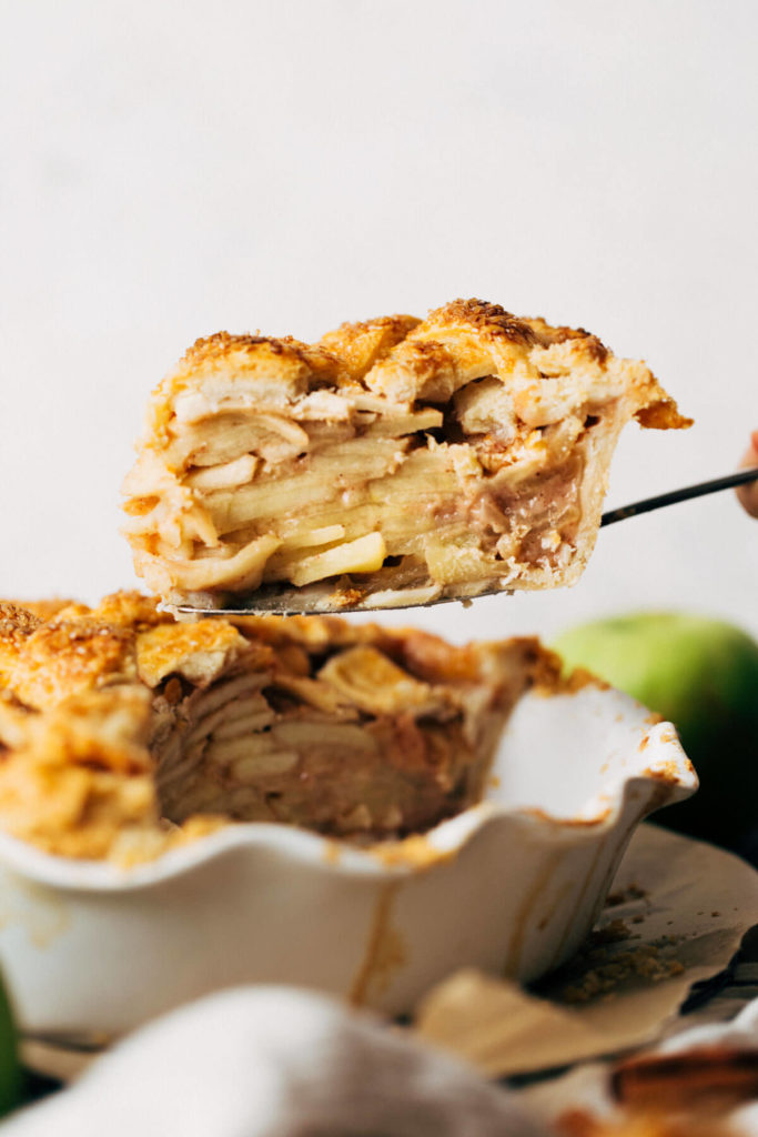 lifting a slice of apple pie out of the pie