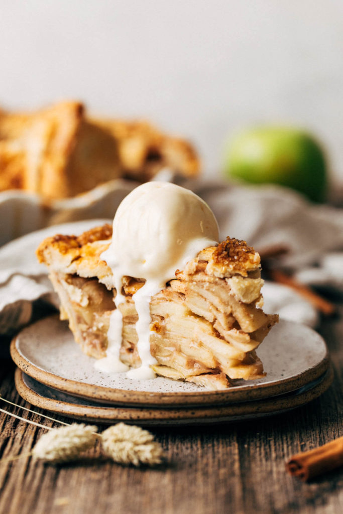 a slice of apple pie on a place topped with melting ice cream