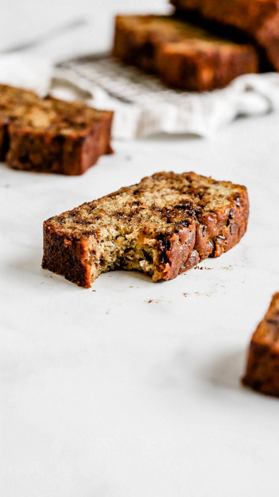 a slice of moist chocolate chip banana bread with a bite taken out
