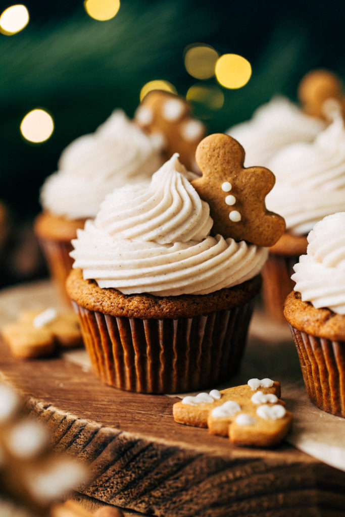 close up on a gingerbread cupcake topped with a mini gingerbread cookie