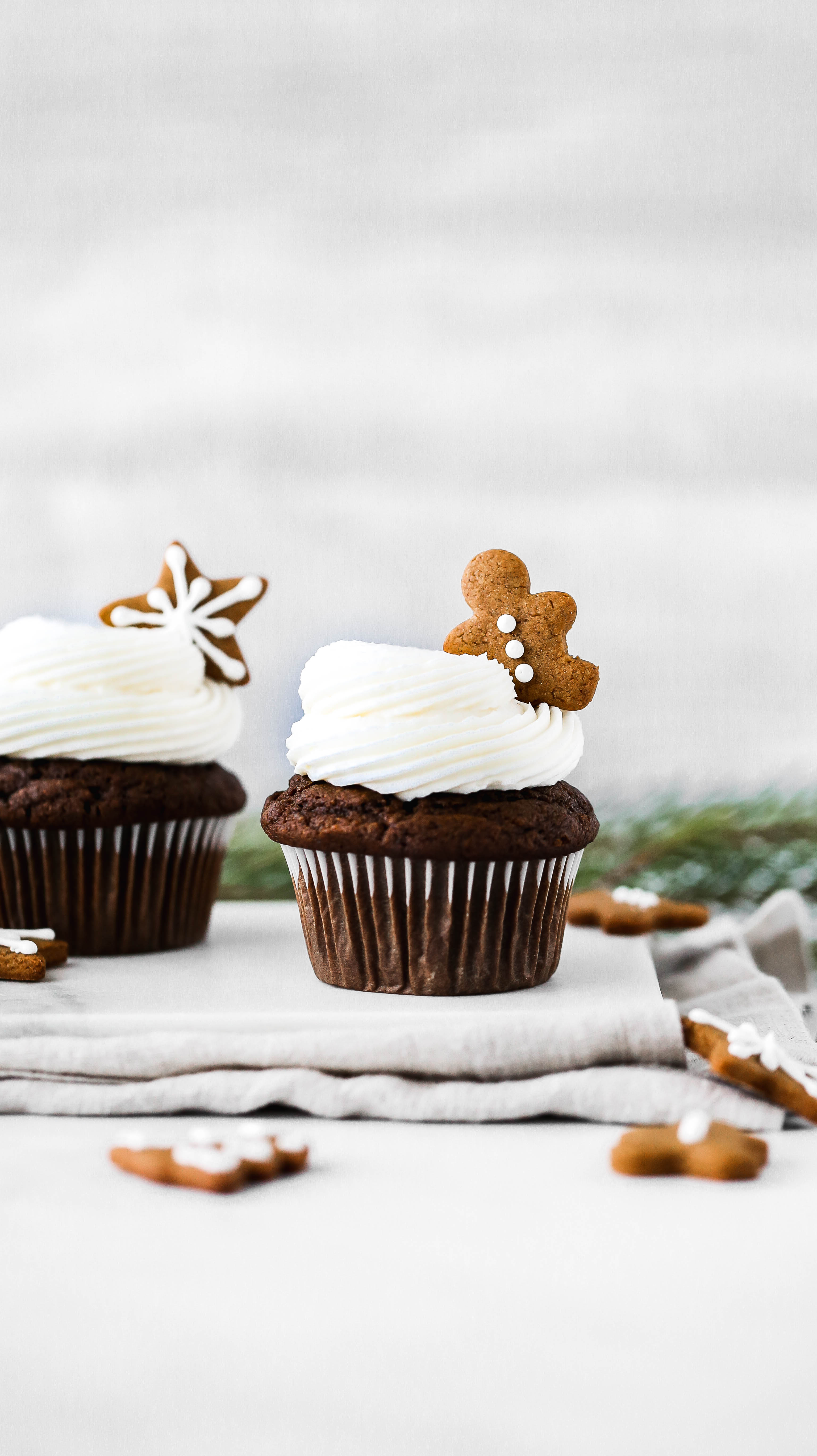 a gingerbread cupcake with a tiny gingerbread cookie on top