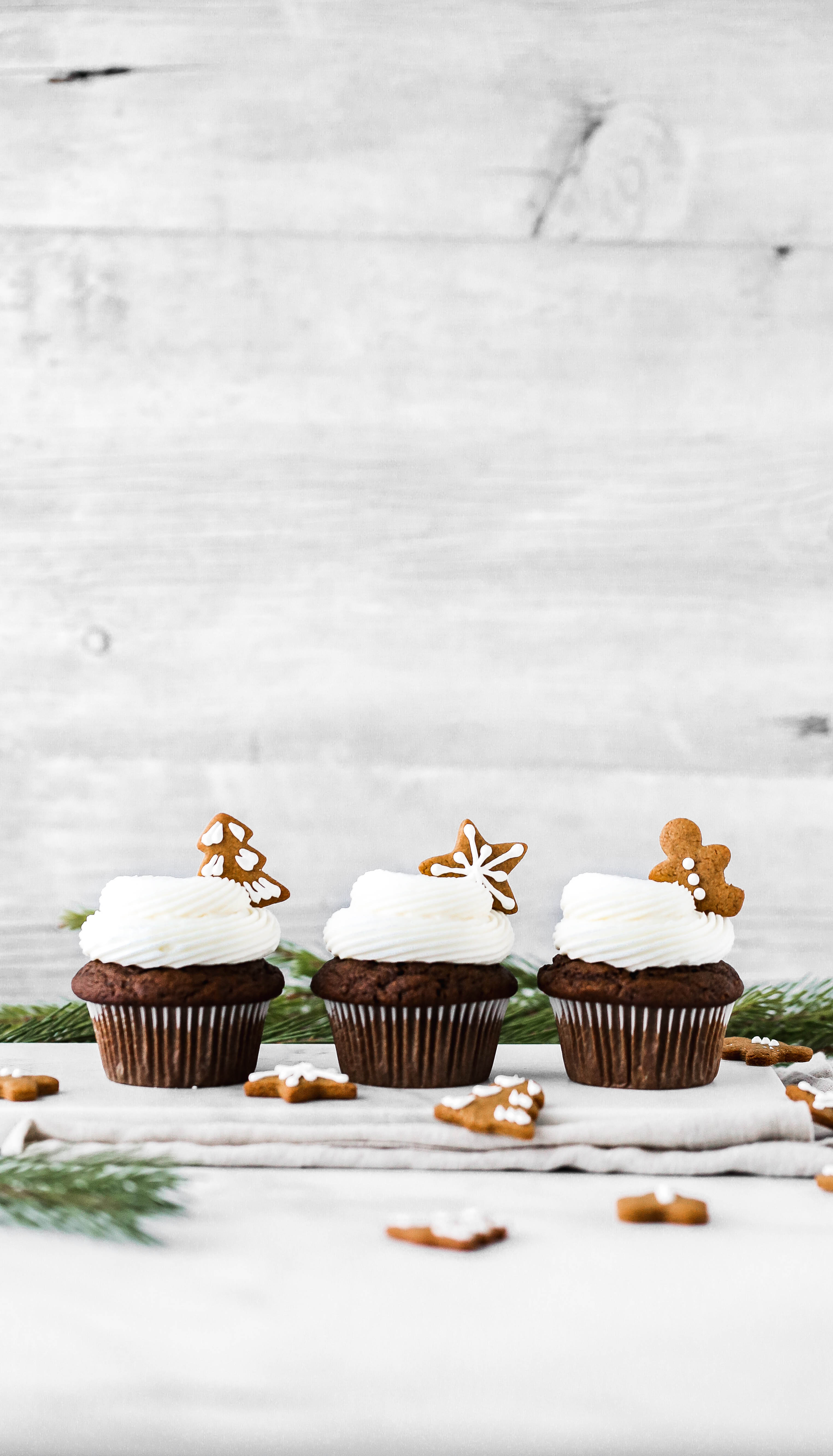 three gingerbread cupcakes on a serving board