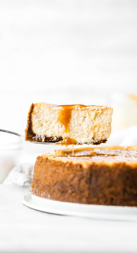 a slice being taken out of a salted caramel cheesecake