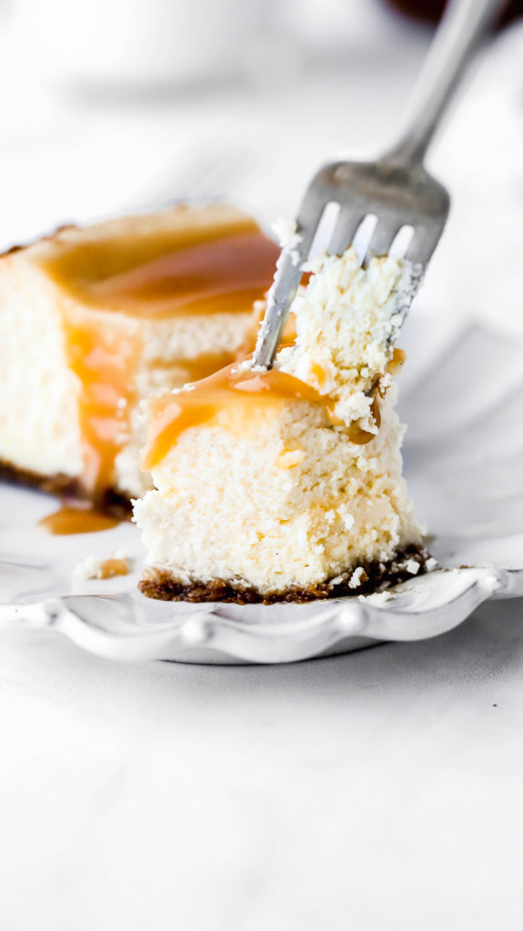a bite being taken out of a slice of salted caramel cheesecake