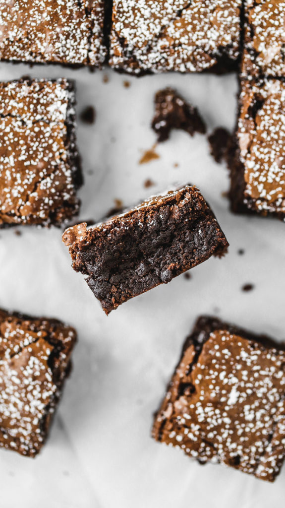 chocolate brownies scattered on a sheet of parchment paper