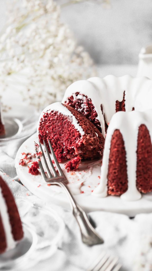 a partially eaten slice of red velvet bundt cake with cream cheese icing