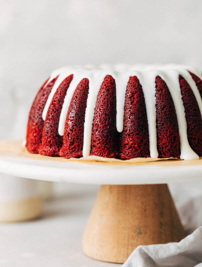 red velvet bundt cake from the side with glaze dripping down