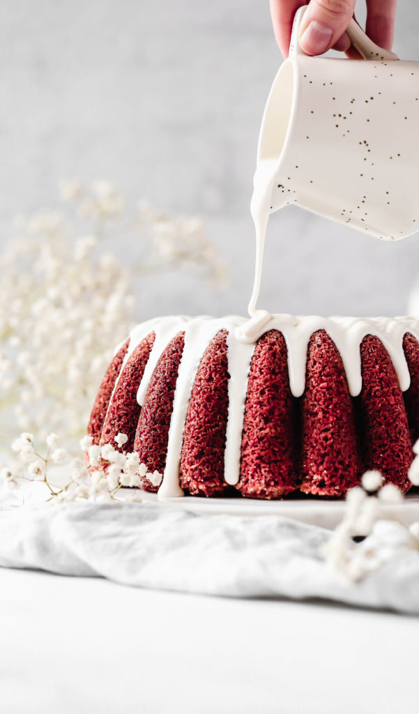 drizzling a cream cheese glaze onto a red velvet bundt cake