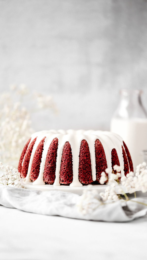 a red velvet bundt cake covered in a cream cheese glaze
