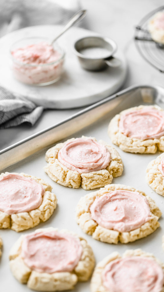 soft frosted sugar cookies on a baking tray