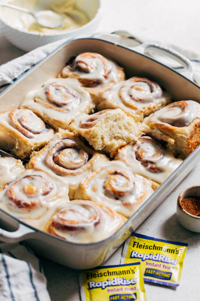 baked and iced cinnamon rolls in a baking pan