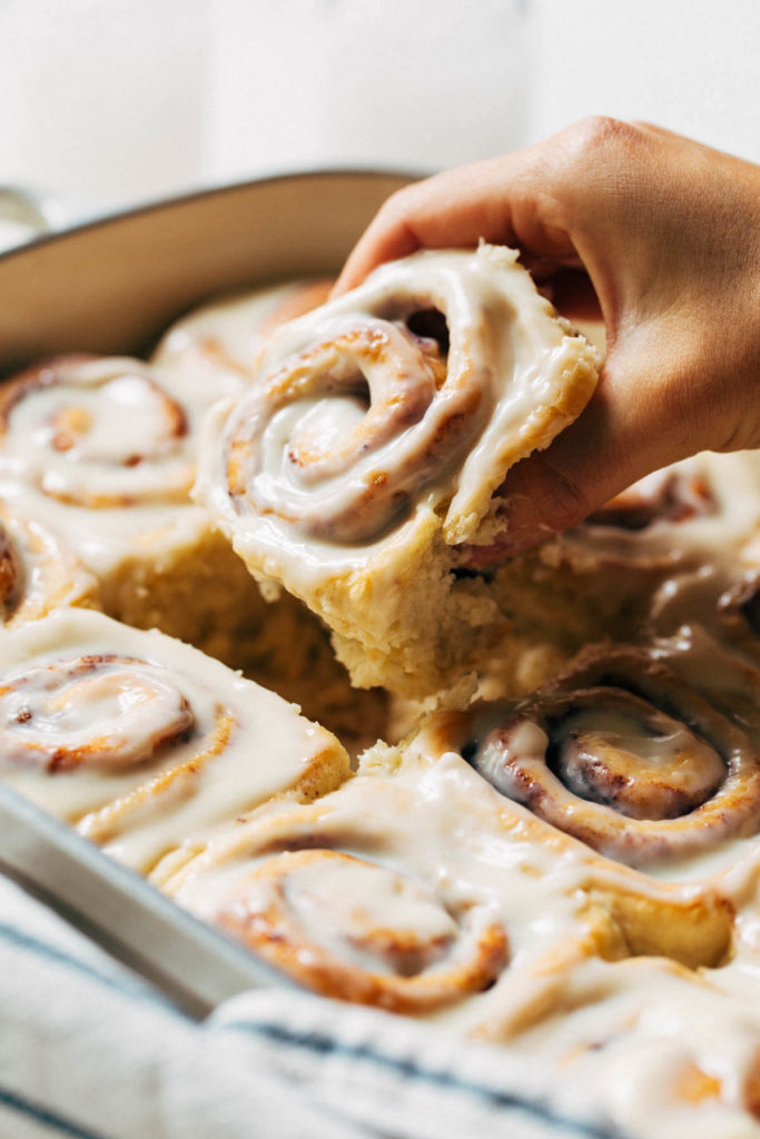 lifting a cinnamon roll out of a baking pan