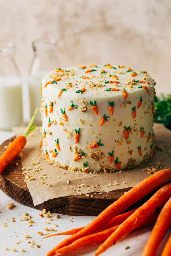 a carrot cake decorated with frosting carrots on a rustic wood board