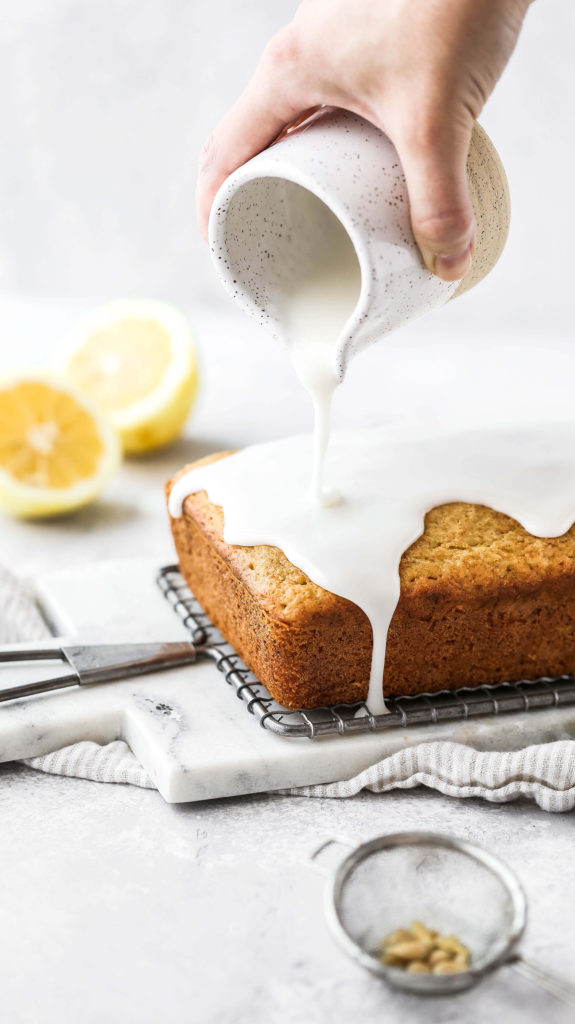 lemon glaze being drizzled on a lemon zucchini bread loaf