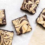 peanut butter swirl brownies scattered on parchment paper