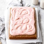 a strawberry cake with swirls of strawberry cream cheese frosting on top