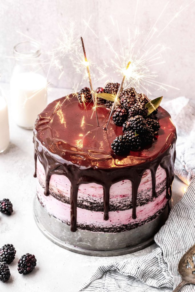 a layered blackberry chocolate cake with sparklers