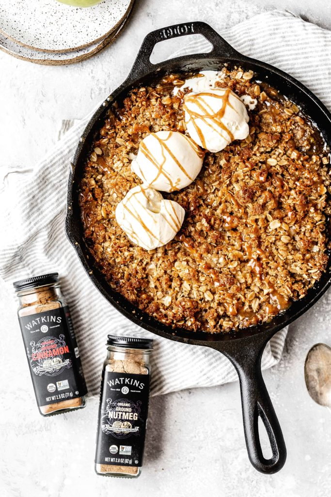 a cast iron skillet of apple crisp with ice cream on top