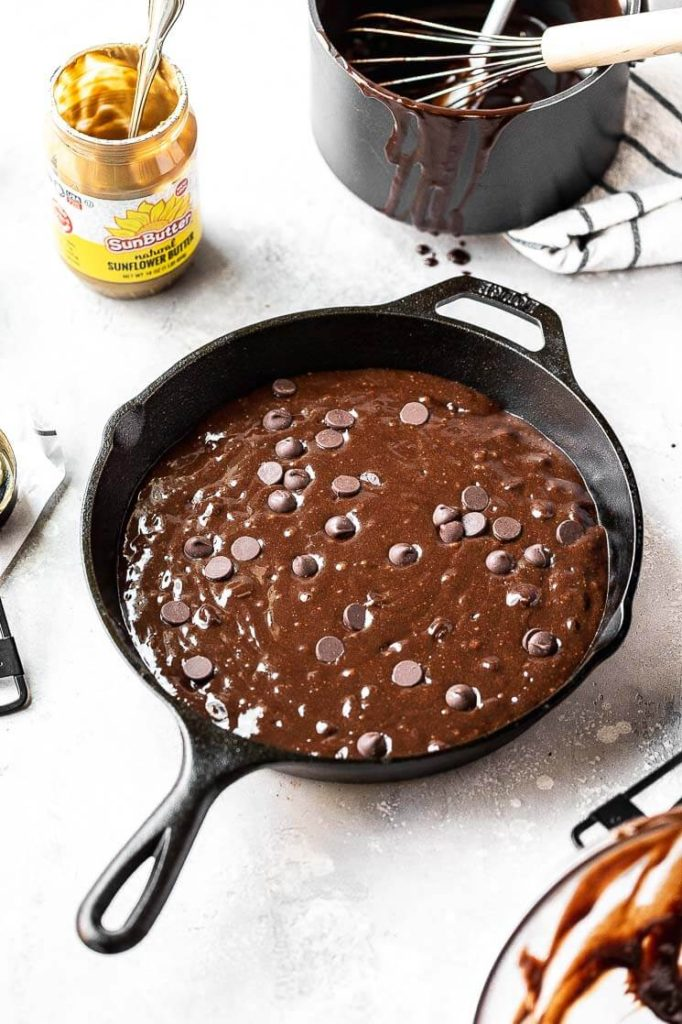 brownie batter ready to bake in a cast iron skillet