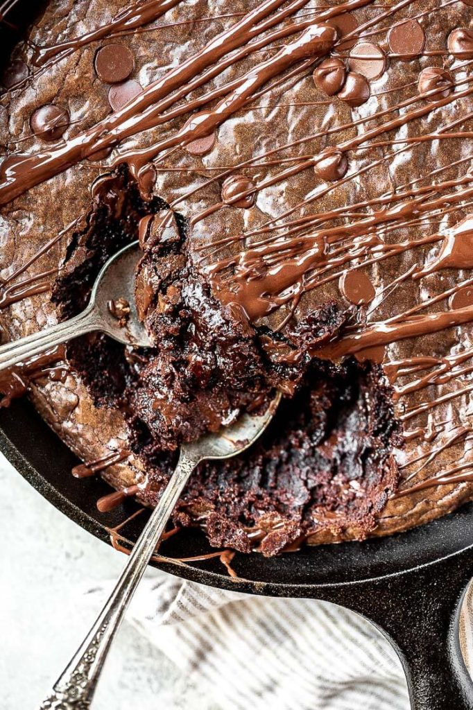 spoons digging into a large skillet brownie