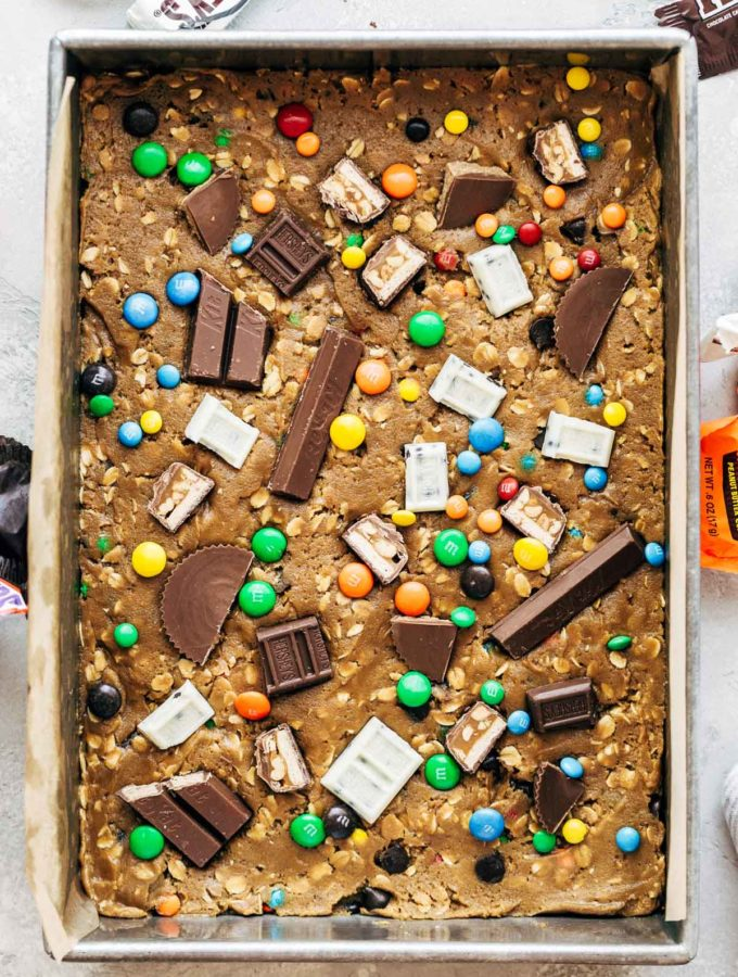 cookie dough pressed into a pan with halloween candy on top