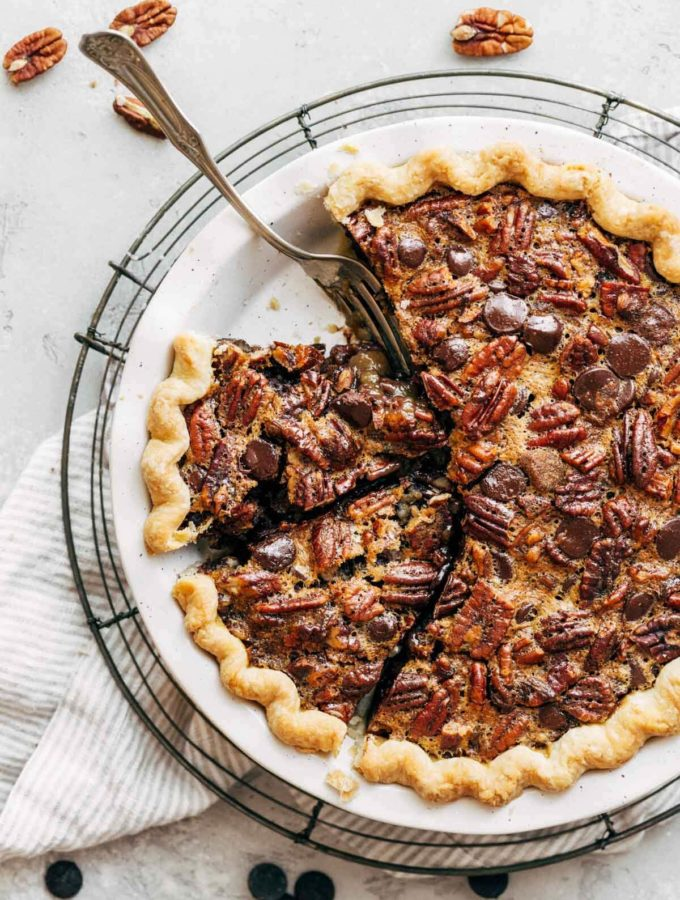 a whole and sliced chocolate bourbon pecan pie