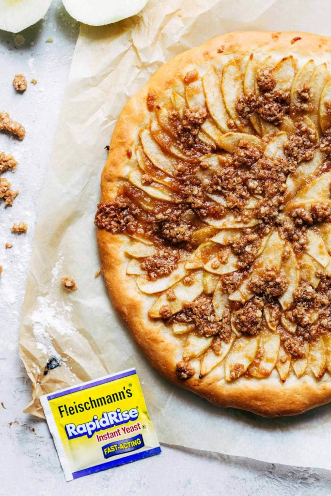 a freshly baked apple dessert pizza on parchment paper