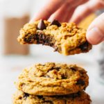 lifting the top cookie from a stack of vegan pumpkin cookies