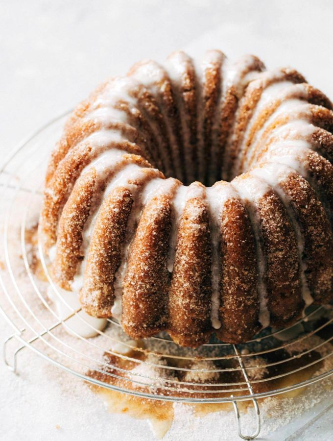 an apple cider bundt cake on a round wire cooling rack