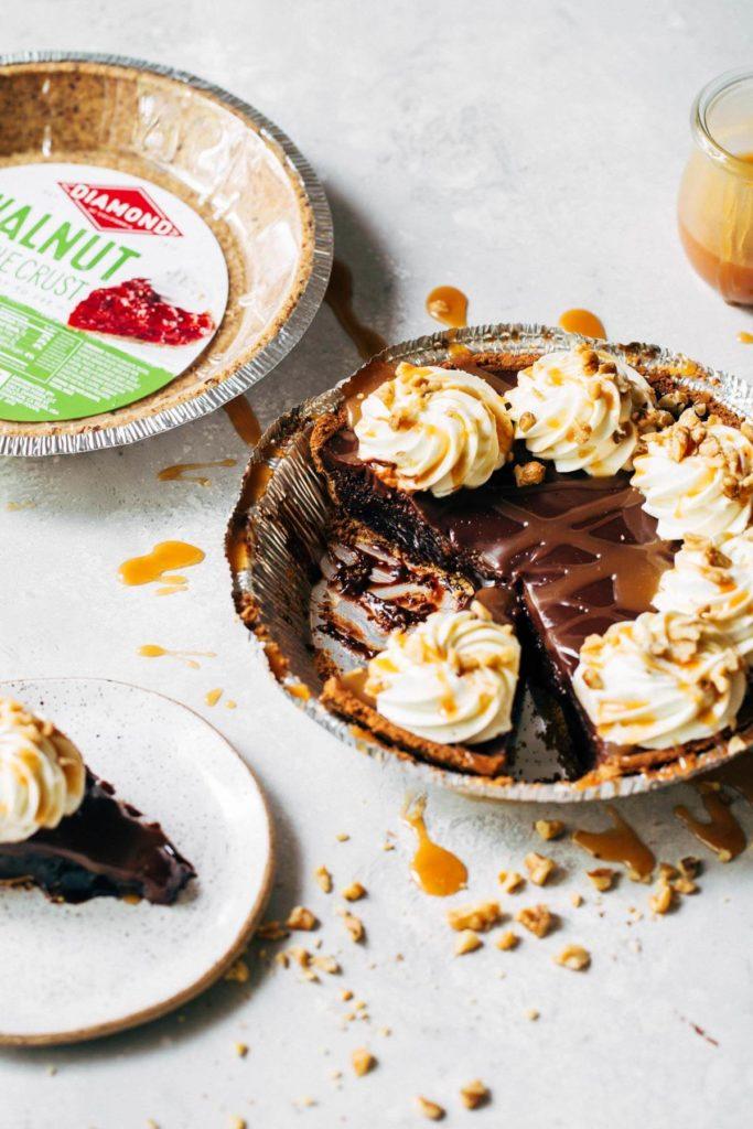 a sliced brownie pie next to a walnut crust
