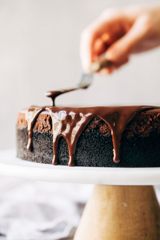 chocolate ganache dripping off the side of a cheesecake