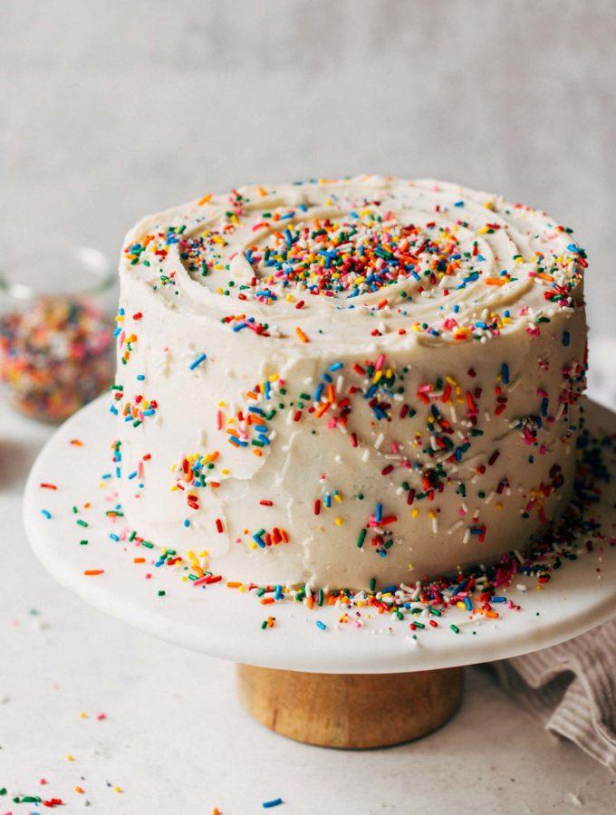 a funfetti layer cake on a cake stand