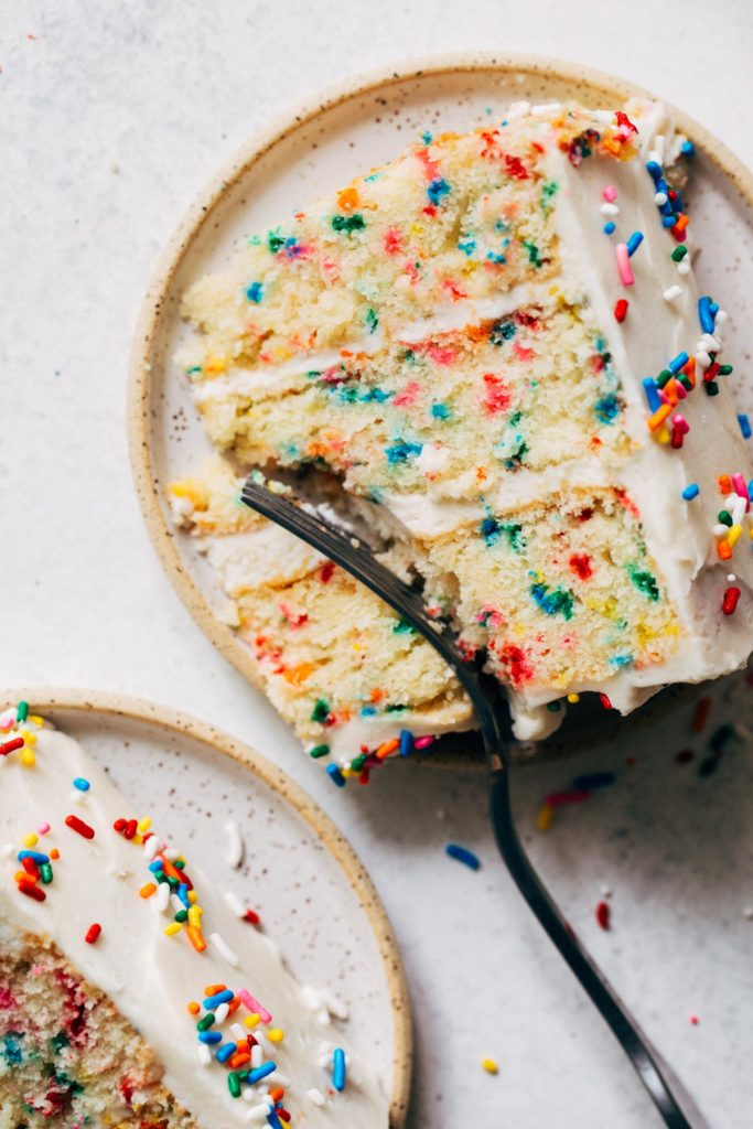 a slice of funfetti cake on a ceramic plate
